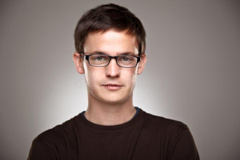Retrato de um menino normal com vidros orlarados em um fundo cinzento imagens de stock