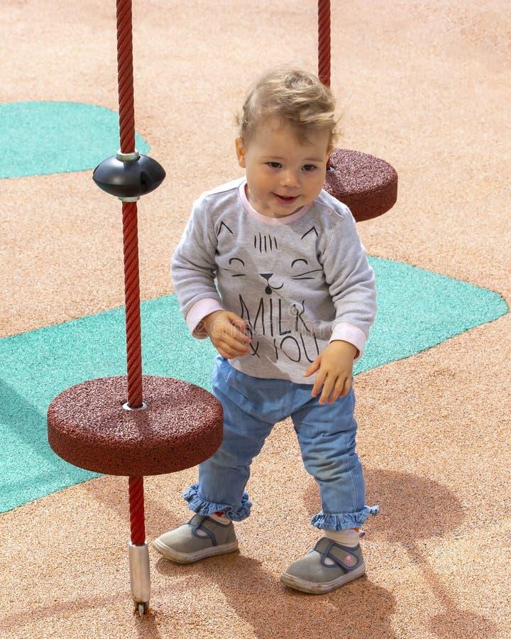 Retrato de um menino pequeno da menina do bebê de um ano da criança no campo de jogos, caucasiano com o cabelo encaracolado, vert imagem de stock royalty free