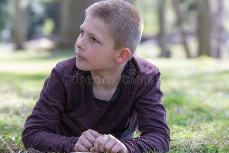 Retrato de um menino que encontra-se na grama no jardim em um dia de verão que olha ao lado foto de stock royalty free
