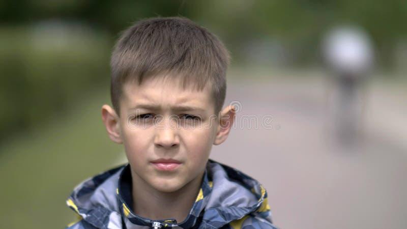 Retrato de um menino sério com um relance do tence que olha a câmera, cara pesada do close-up fotos de stock royalty free