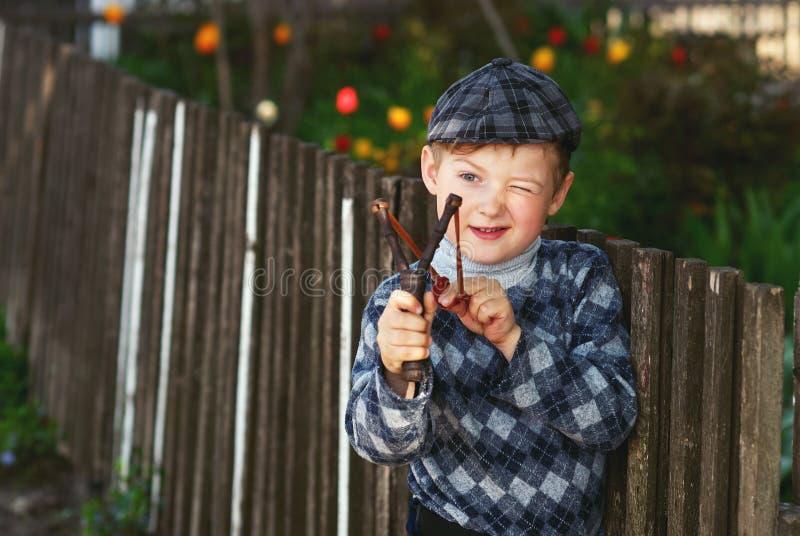 Retrato de um menino, uma criança que guarda um estilingue fotos de stock royalty free