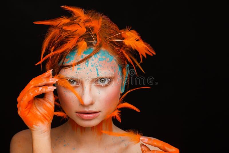 Retrato de um modelo bonito com composição criativa e do penteado usando penas alaranjadas imagens de stock royalty free