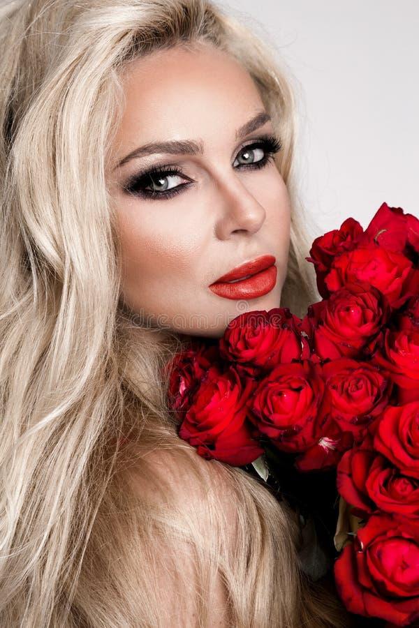 Retrato de um modelo fêmea louro bonito com cabelo longo, bonito Modelo na roupa interior 'sexy', guardando rosas vermelhas fotografia de stock royalty free