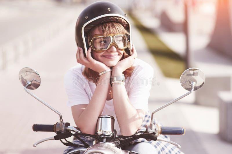 Retrato de um moderno bonito da menina que senta-se em um 'trotinette' retro preto, levantamento de sorriso e para apreciar a luz imagens de stock royalty free