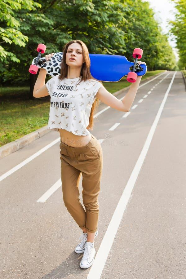 Retrato de um moderno elegante da moça que esteja guardando um skate para golovoy skateboarding lifestyle fotografia de stock