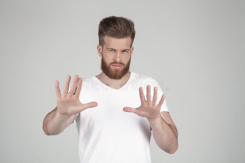 Retrato de um moderno 'sexy' bonito vestido em um t-shirt branco Guarda suas mãos antes de ele e diz a parada batente fotografia de stock royalty free