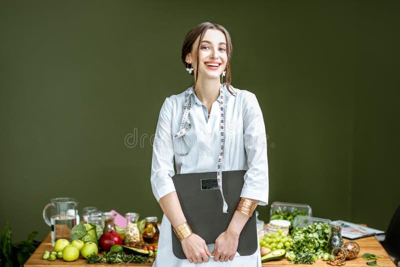 Retrato de um nutricionista da mulher com pesos e alimento saudável dentro imagens de stock royalty free