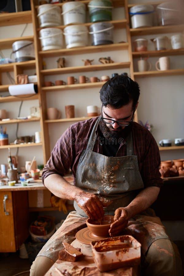 Retrato de um oleiro masculino no avental que trabalha em seu estúdio, foco seletivo, close-up foto de stock royalty free