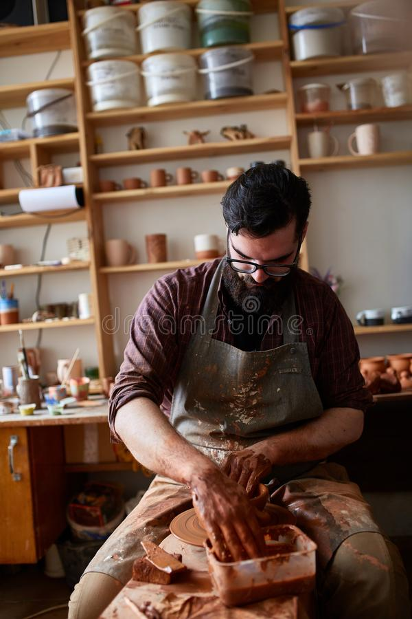 Retrato de um oleiro masculino no avental que trabalha em seu estúdio, foco seletivo, close-up fotos de stock royalty free