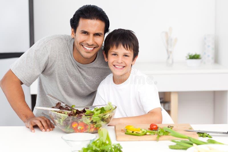 Retrato de um pai e de seu filho que preparam uma salada foto de stock royalty free