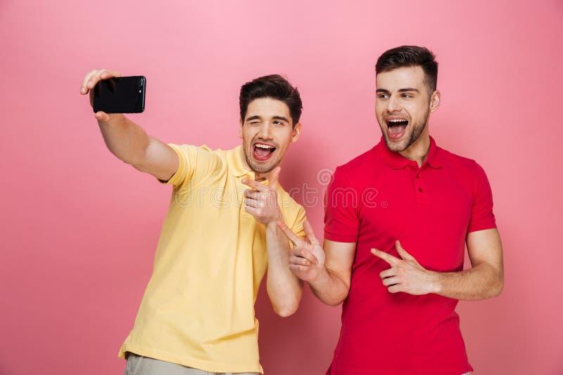 Retrato de um par alegre feliz que toma um selfie fotografia de stock