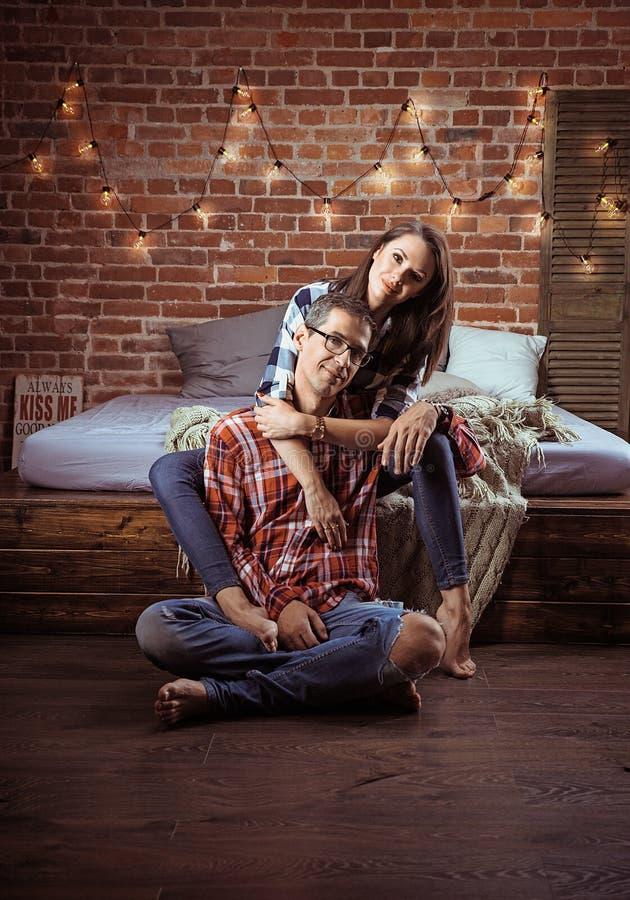 Retrato de um par alegre relaxado em um interior moderno imagens de stock