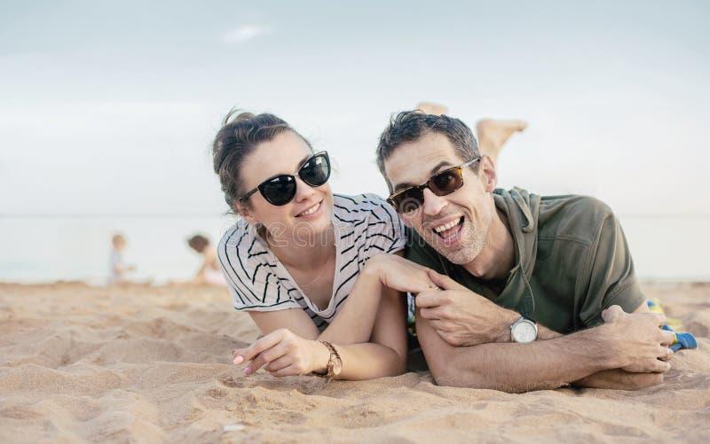 Retrato de um par alegre, relaxado que coloca na areia imagens de stock