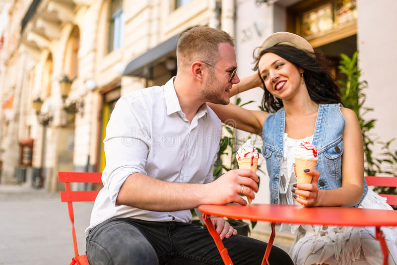 Retrato de um par de sorriso que come o gelado e que tem o divertimento fotografia de stock