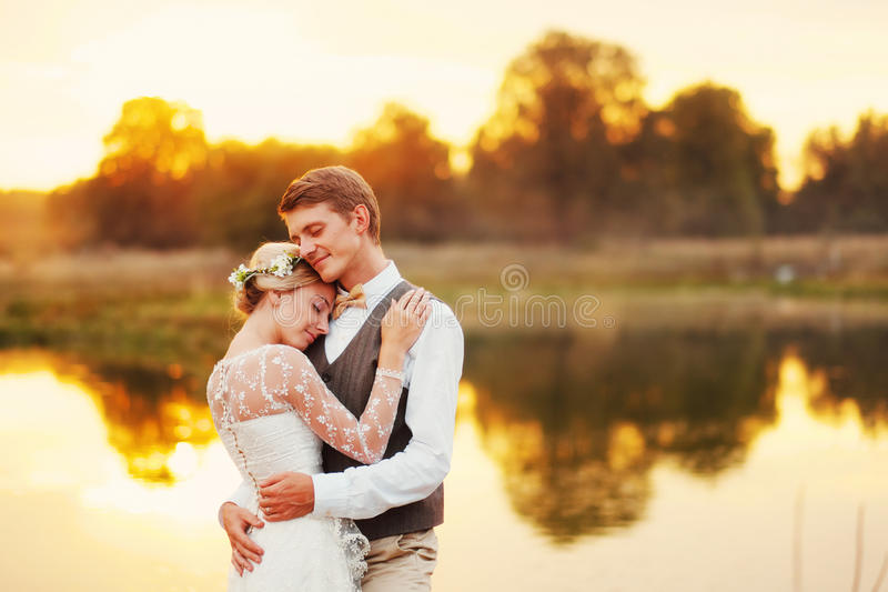 Retrato de um par do casamento na perspectiva da água no sol do por do sol No fundo um lago fotografia de stock