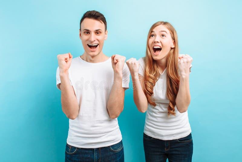 Retrato de um par entusiasmado, de um homem e de uma mulher comemorando a vitória com os punhos aumentados, gritando, em um claro foto de stock royalty free