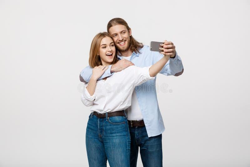 Retrato de um par feliz que faz a foto do selfie com o smartphone sobre o fundo branco do estúdio fotografia de stock royalty free
