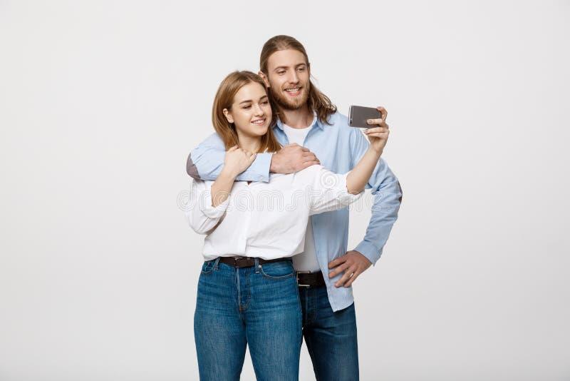 Retrato de um par feliz que faz a foto do selfie com o smartphone sobre o fundo branco do estúdio imagem de stock royalty free