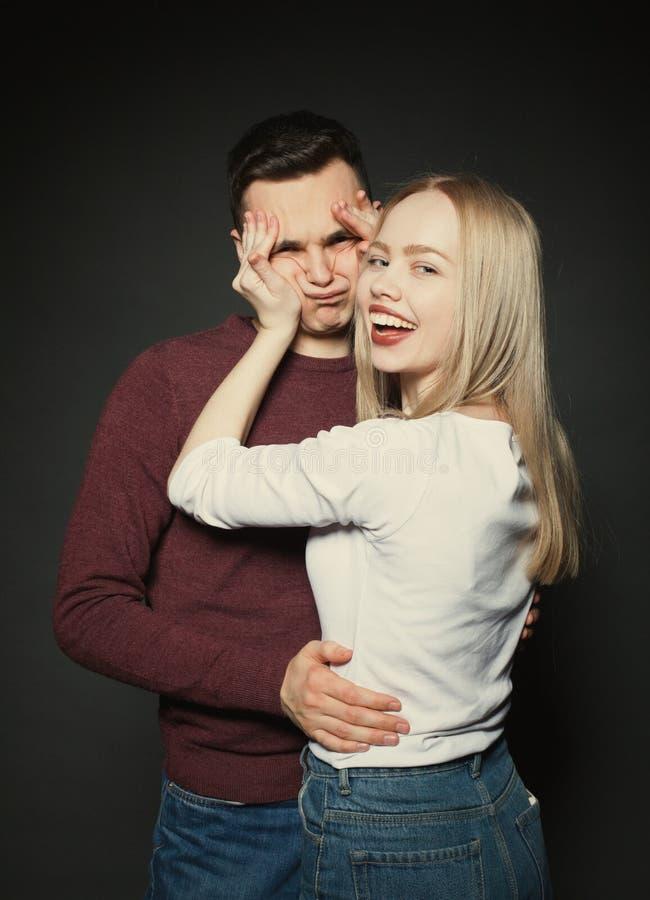 Retrato de um par novo bonito no amor que levanta no estúdio sobre o fundo escuro A menina joga com a cara de seu noivo foto de stock