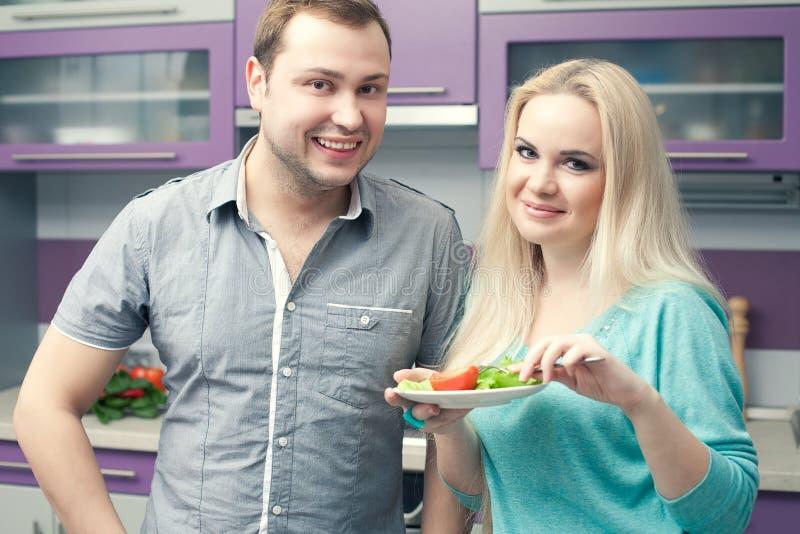 Retrato de um par novo bonito que está em sua cozinha foto de stock