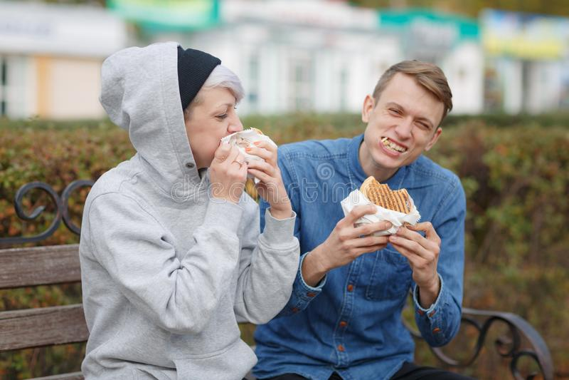 Retrato de um par novo com fome que coma hamburgueres em um parque em um banco e em um sorriso imagem de stock royalty free