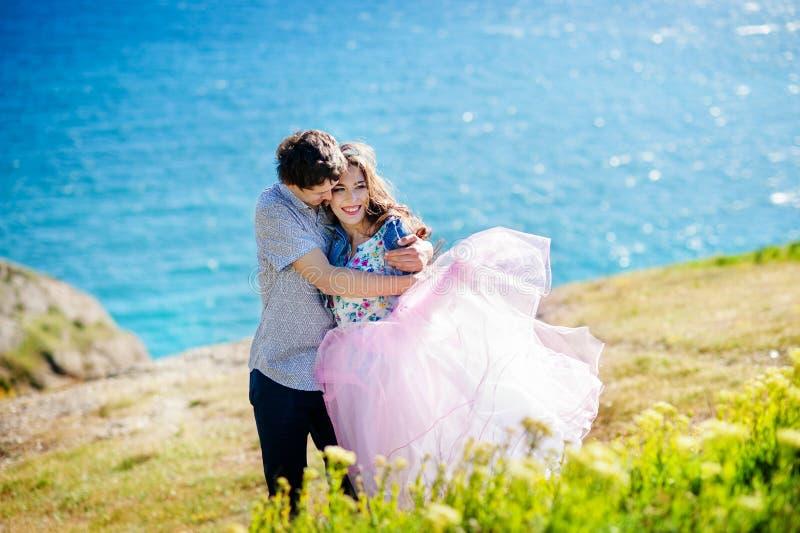 Retrato de um par novo feliz que aprecia um dia no parque perto do mar junto imagens de stock royalty free