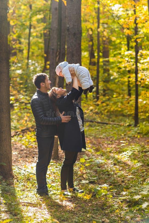 Retrato de um par novo feliz que joga com seu bebê recém-nascido bonito imagem de stock royalty free