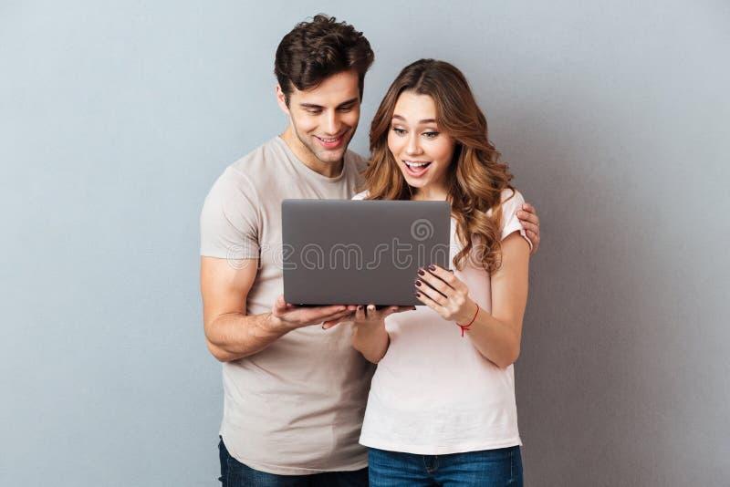 Retrato de um par novo feliz usando o laptop fotos de stock royalty free