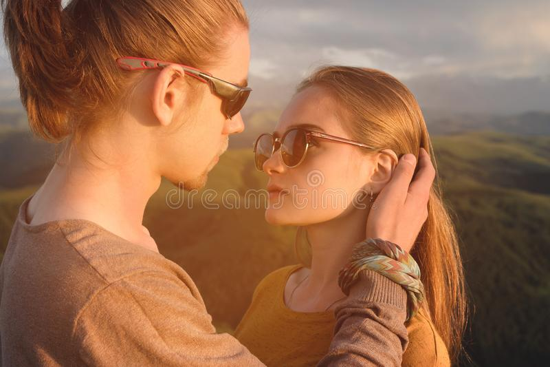 Retrato de um par novo romântico na natureza Um homem e uma menina nos óculos de sol olham se com olhares de amor sobre foto de stock royalty free