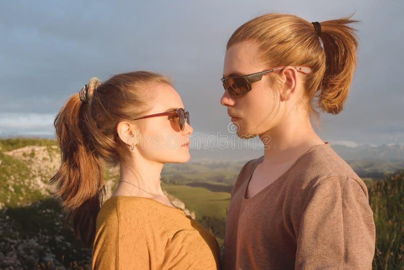 Retrato de um par novo romântico na natureza Um homem e uma menina nos óculos de sol olham se com olhares de amor sobre imagem de stock
