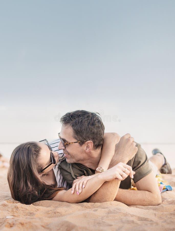 Retrato de um par romântico que relaxa em uma praia fotos de stock