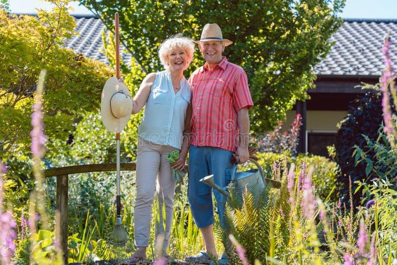 Retrato de um par superior ativo que guarda ferramentas de jardinagem no jardim imagens de stock