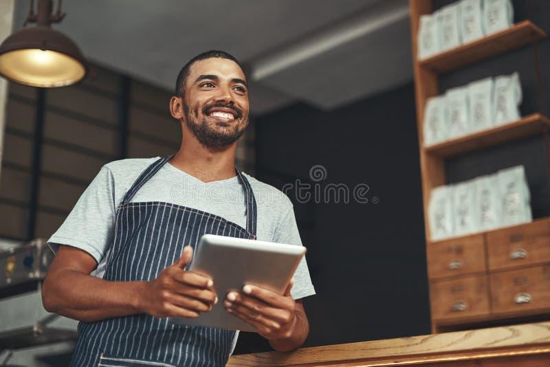 Retrato de um proprietário empresarial novo em seu café foto de stock