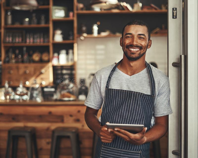 Retrato de um proprietário masculino que guarda a tabuleta digital em seu café fotos de stock