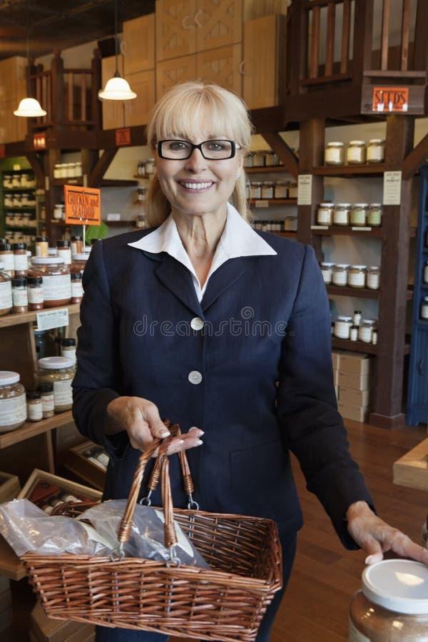 Retrato de um proprietário superior feliz que está com a cesta completa das especiarias na loja foto de stock