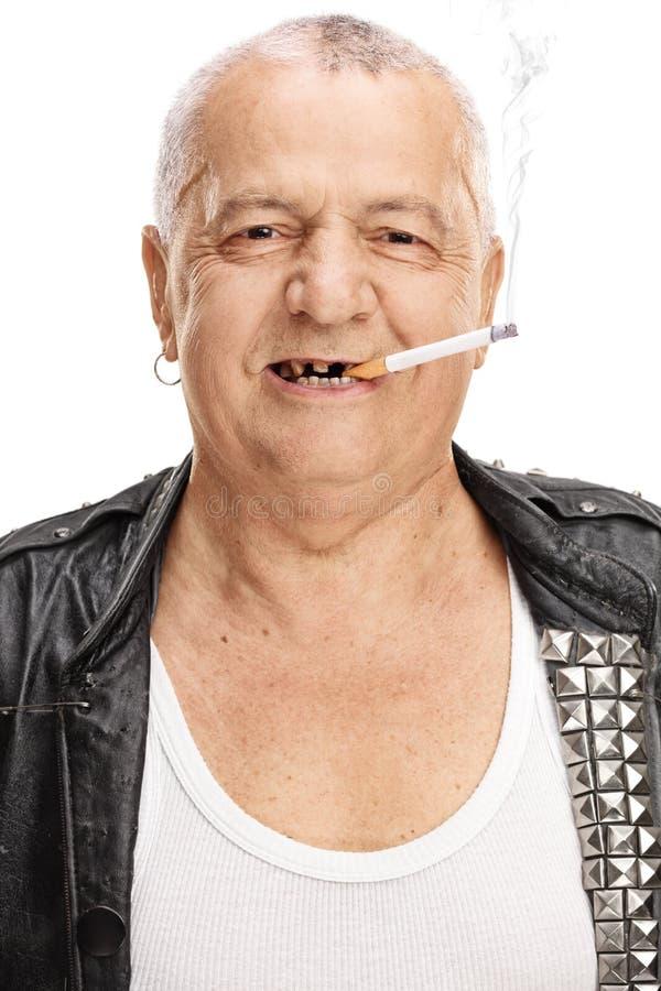 Retrato de um punker idoso com um cigarro fotografia de stock royalty free