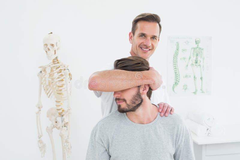 Retrato de um quiroprático masculino que faz o ajuste do pescoço fotos de stock royalty free