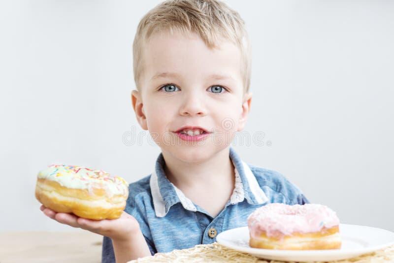 Retrato de um rapaz pequeno bonito que come anéis de espuma foto de stock