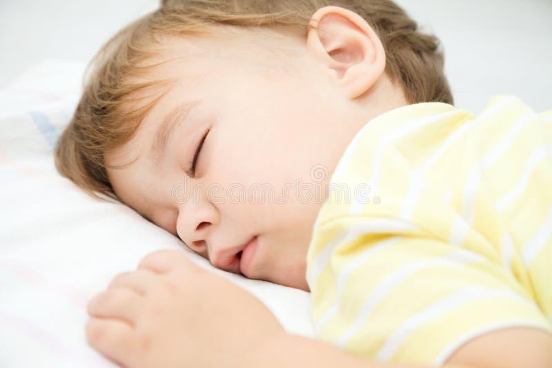 O rapaz pequeno bonito está dormindo fotografia de stock