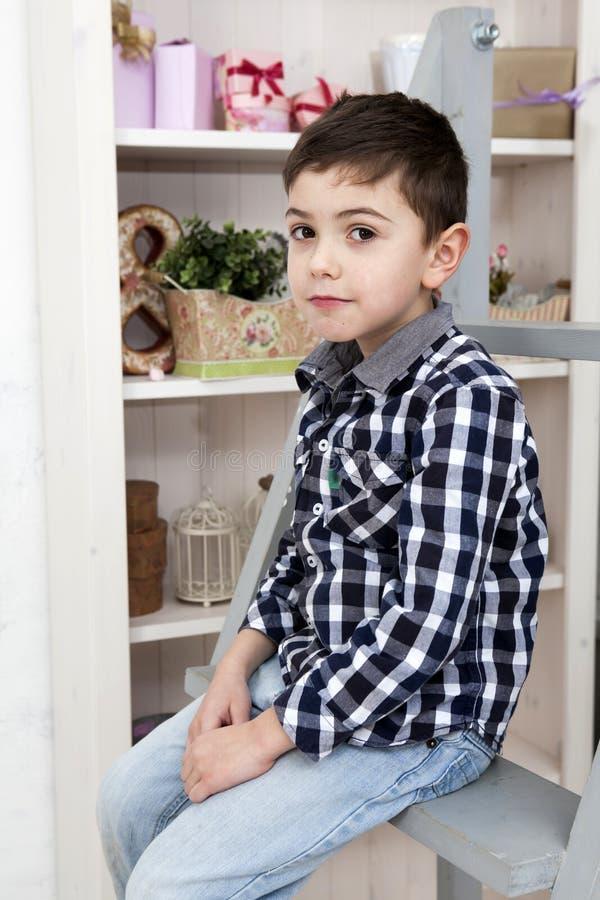 Retrato de um rapaz pequeno bonito que senta-se na escadaria imagens de stock