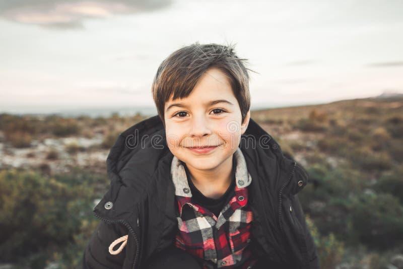 Retrato de um rapaz pequeno com expressão engraçada e do sorriso no campo Criança feliz foto de stock