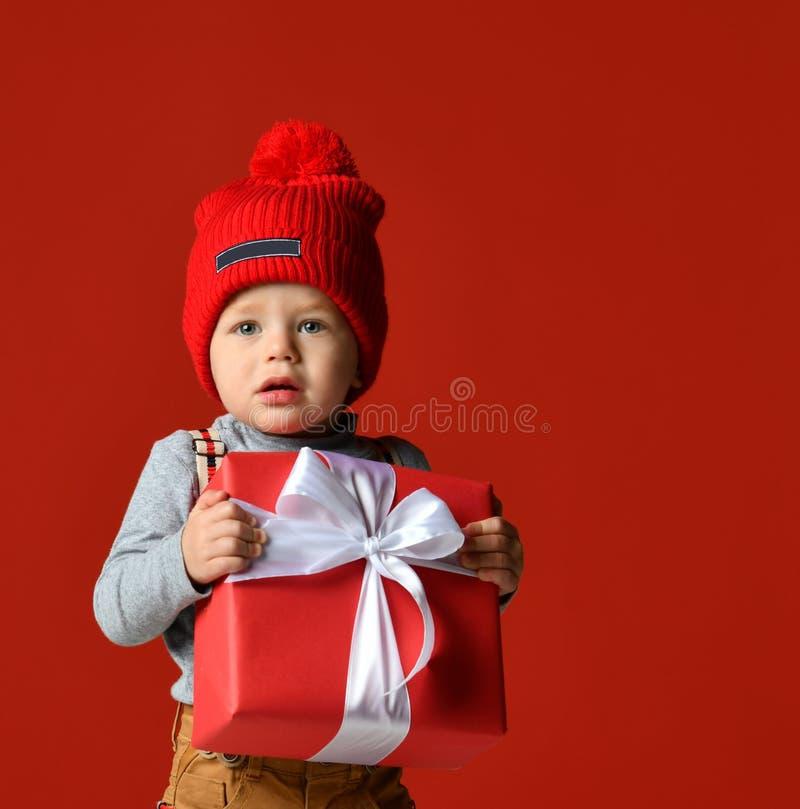 Retrato de um rapaz pequeno com um pompon guardando uma grande caixa de presente com uma curva branca imagens de stock