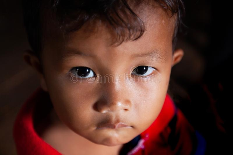 Retrato de um rapaz pequeno do Khmer com luz do ponto que aponta nele, olhos roxos bonitos que olham acima na câmera imagens de stock