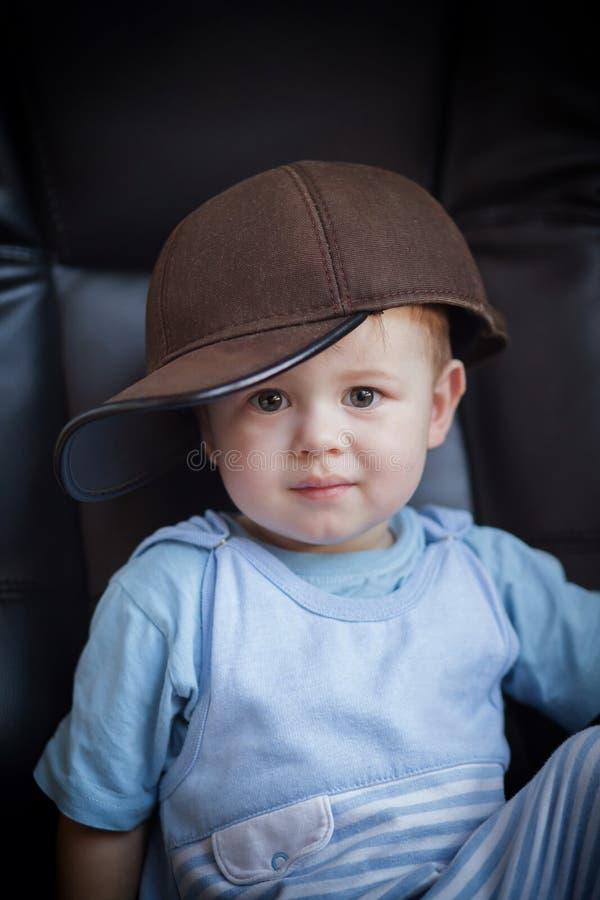 Retrato de um rapaz pequeno em um tampão fotografia de stock