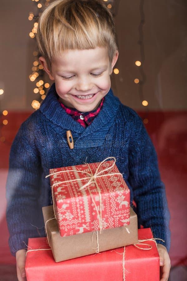 Retrato de um rapaz pequeno feliz que guarda um presente novo Natal Aniversário imagem de stock