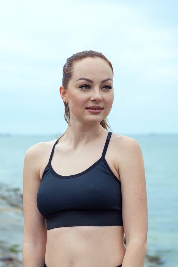 Retrato de um ruivo, menina bonita, atl?tica com sardas em uma parte superior preta na perspectiva do mar, oceano outdoor fotos de stock royalty free