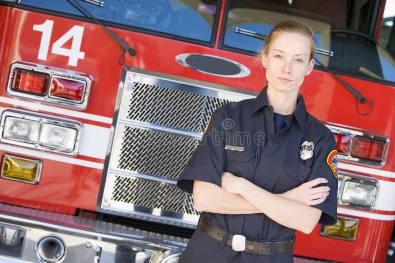 Retrato de um sapador-bombeiro por um motor de incêndio imagens de stock royalty free