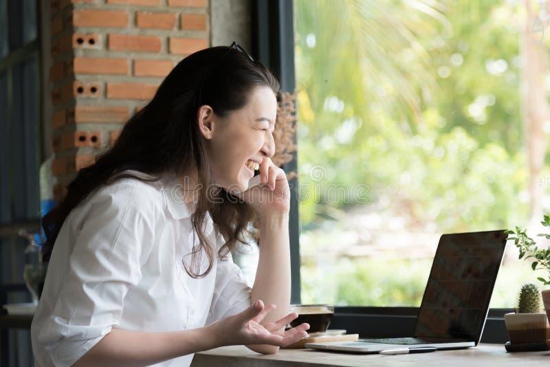 Retrato de um smartphone feliz do Internet do assento e do uso da mulher de negócios com o laptop em seu escritório do local de t fotografia de stock royalty free