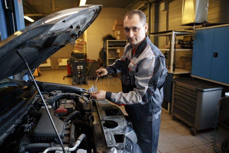 Retrato de um sorriso fixando um motor de automóveis em sua garagem foto de stock royalty free