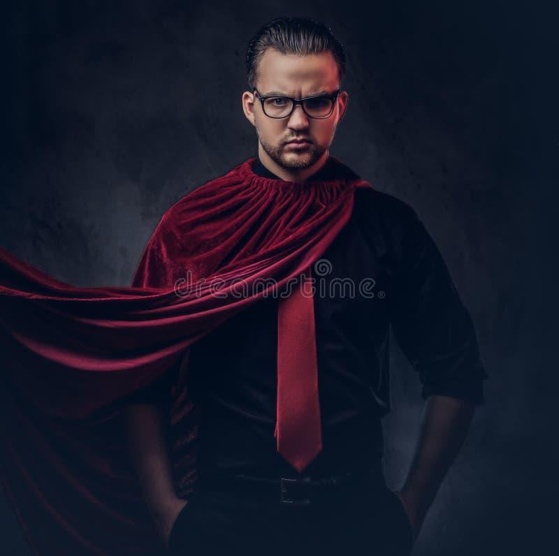 Retrato de um super-herói do bandido do gênio em uma camisa preta com um laço vermelho foto de stock royalty free
